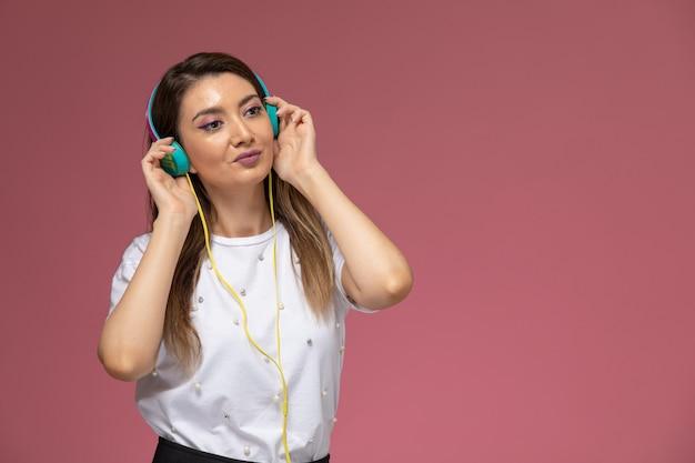 Mulher jovem de camisa branca ouvindo música na parede rosa de frente, modelo de pose de mulher de cor Foto gratuita