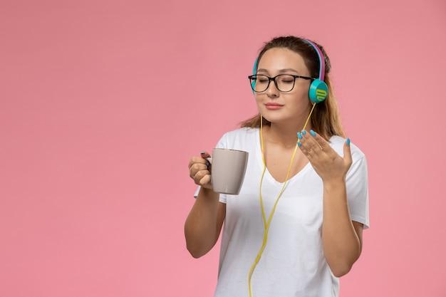 Mulher jovem de camiseta branca, de frente, ouvindo música nos fones de ouvido e segurando uma xícara com chá no fundo rosa Foto gratuita