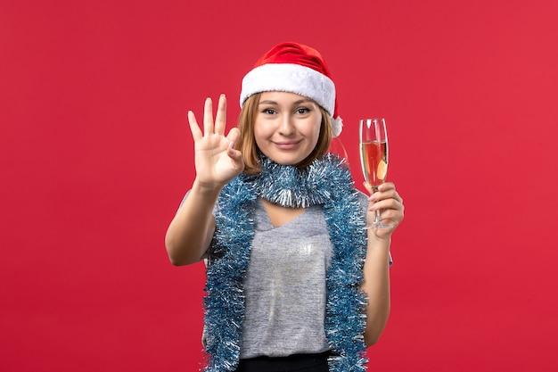 Mulher jovem, de frente, contando, mostrando o número na cor vermelha, feriado de natal Foto gratuita