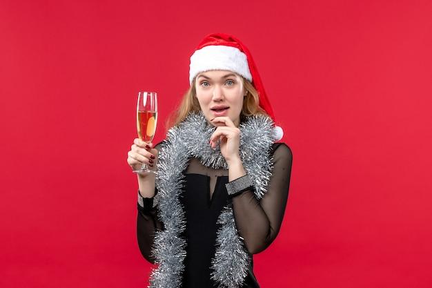 Mulher jovem de frente para celebrar o ano novo na parede vermelha férias natal emoção Foto gratuita