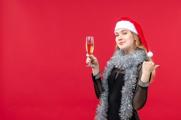 Mulher jovem de frente para comemorar o ano novo na parede vermelha férias emoção natal Foto gratuita