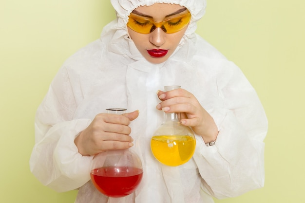 Mulher jovem de frente para o terno especial branco e capacete amarelo segurando frascos com soluções no espaço verde Foto gratuita