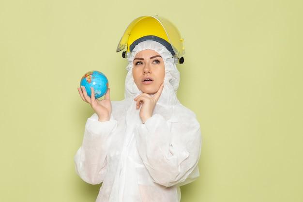 Mulher jovem de frente para o terno especial branco e capacete protetor amarelo segurando o pequeno globo pensando no espaço verde Foto gratuita