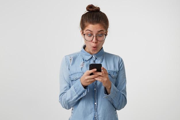 Mulher jovem de óculos olhando, segurando nas mãos um smartphone, os olhos bem abertos e a boca arredondada em surpresa Foto gratuita