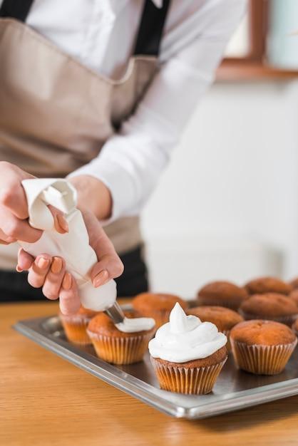 Mulher jovem, decorando, cupcakes, com, branca, creme chicoteado, apertando, a, confeitaria, saco Foto gratuita