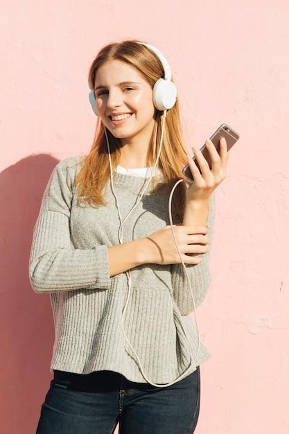 Mulher jovem, desfrutando, a, música, ligado, auscultadores, através, smartphone, contra, fundo cor-de-rosa Foto gratuita