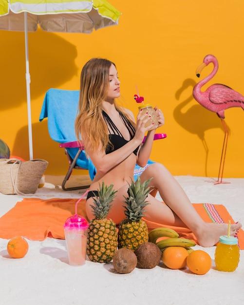 Mulher jovem, desfrutando, coquetel, ligado, praia Foto gratuita
