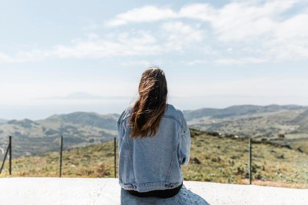 Mulher jovem, desfrutando, vista, de, montanhas Foto gratuita