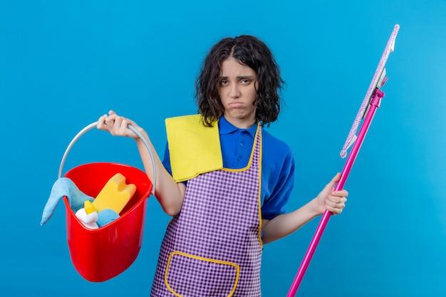 Mulher jovem, desgastar avental, segurando balde, com, ferramentas limpeza, e, esfregão, olhar, excesso de trabalho, e cansado, soprando, bochechas, parede azul Foto gratuita