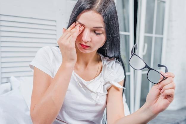 Mulher jovem, desgastar, óculos, tocar, dela, olhos, com, mão Foto gratuita