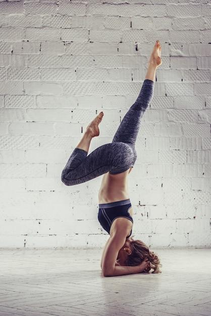 Mulher jovem desportiva, fazendo exercícios de ioga, isolado no fundo branco Foto Premium