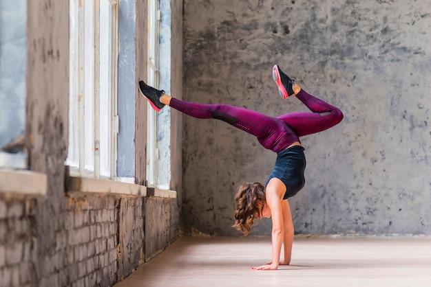 Mulher jovem desportiva fazendo pose de árvore virada para baixo no sótão Foto gratuita