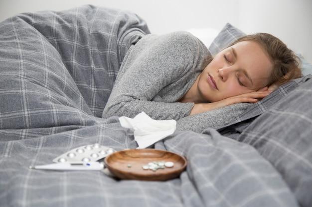 Mulher jovem doente deitada na cama, dormindo Foto gratuita