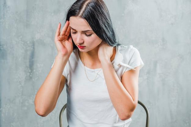 Mulher jovem doente sentado contra o pano de fundo cinzento, sofrendo de dor de cabeça Foto gratuita