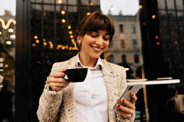 Mulher jovem e animada feliz vestida de jaqueta branca está usando smartphone e fones de ouvido enquanto bebe café nas luzes da cidade. foto de alta qualidade Foto gratuita