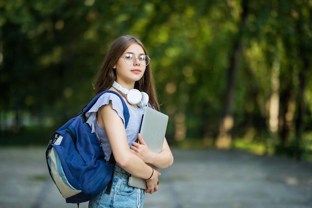 Mulher jovem e atraente alegre com mochila e notebooks em pé e sorrindo no parque Foto gratuita