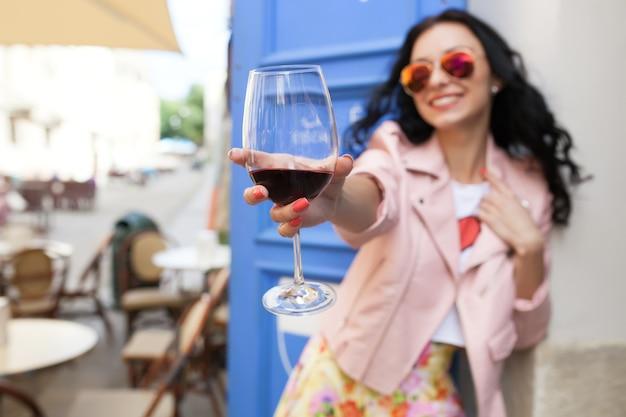 Mulher jovem e atraente bebendo vinho nas férias de verão, sentada em um café de rua da cidade com roupa legal Foto gratuita