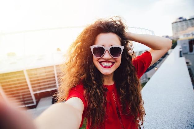 Mulher jovem e atraente com cabelo encaracolado toma um selfie, posando e olhando para a câmera Foto gratuita