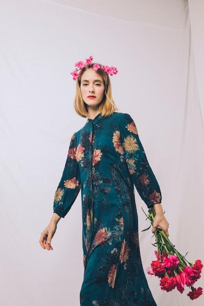 Mulher jovem e atraente com coroa na cabeça e buquê de flores Foto gratuita