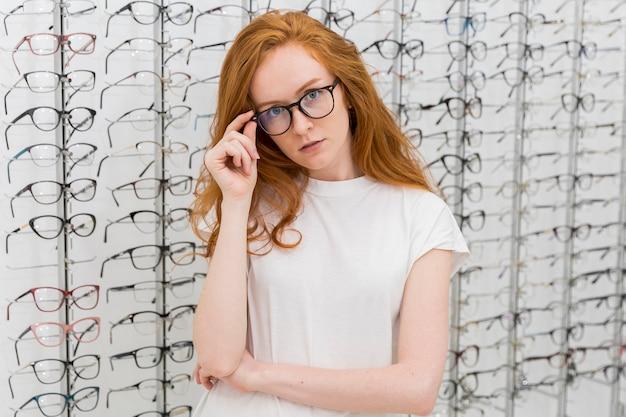 Mulher jovem e atraente com espetáculo na loja de óptica Foto gratuita