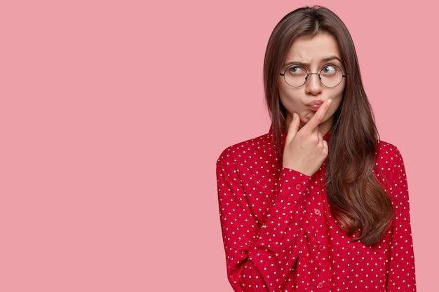 Mulher jovem e atraente com expressão pensativa, pensa na pergunta, sente dúvida, levanta as sobrancelhas, segura o queixo Foto gratuita