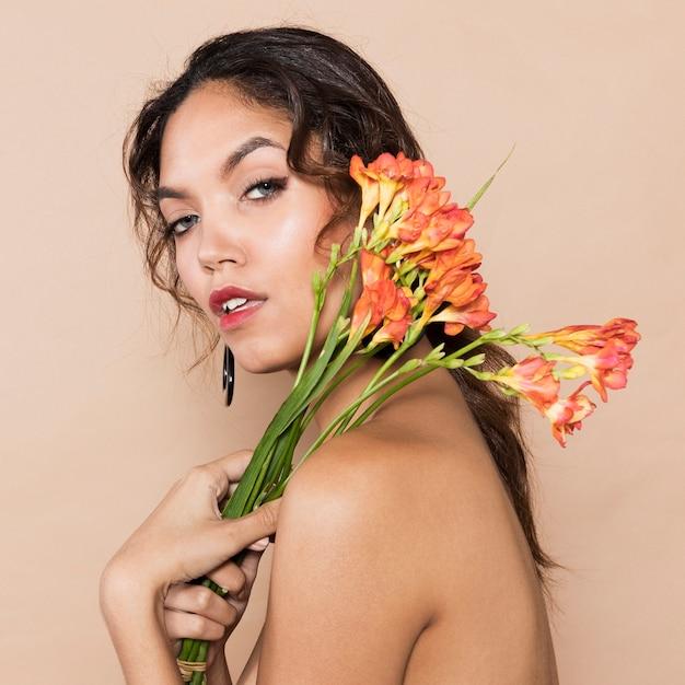 Mulher jovem e atraente com flores por cima do ombro Foto gratuita