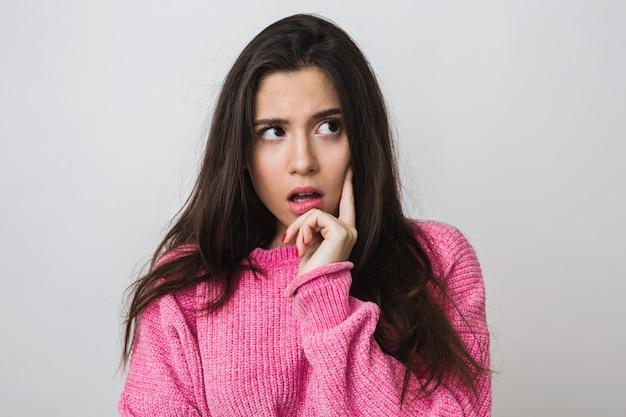 Mulher jovem e atraente com suéter rosa, expressão facial surpresa, boca aberta, pensando, isolado, close-up retrato Foto gratuita