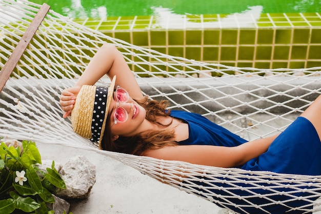 Mulher jovem e atraente com vestido azul e chapéu de palha usando óculos de sol rosa relaxando nas férias deitada na rede com roupa estilo verão, sorrindo feliz Foto gratuita