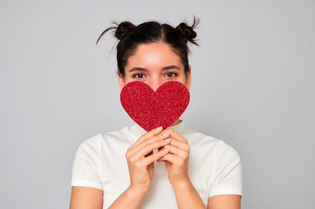 Mulher jovem e atraente de etnia alegre apaixonada segurando um grande dia dos namorados com um coração vermelho brilhante e cobrindo a boca e o nariz enquanto sorri com os olhos Foto Premium