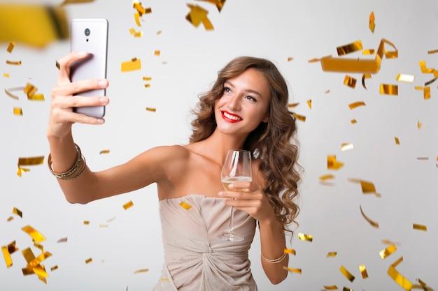 Mulher jovem e atraente elegante comemorando ano novo, bebendo champanhe fazendo selfie foto no telefone, confete dourado voando, sorrindo feliz, isolado, usando vestido de festa Foto gratuita