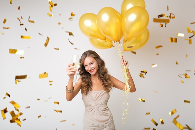 Mulher jovem e atraente elegante comemorando o ano novo, bebendo champanhe segurando balões de ar, confetes dourados voando, sorrindo feliz, isolada, usando vestido de festa Foto gratuita