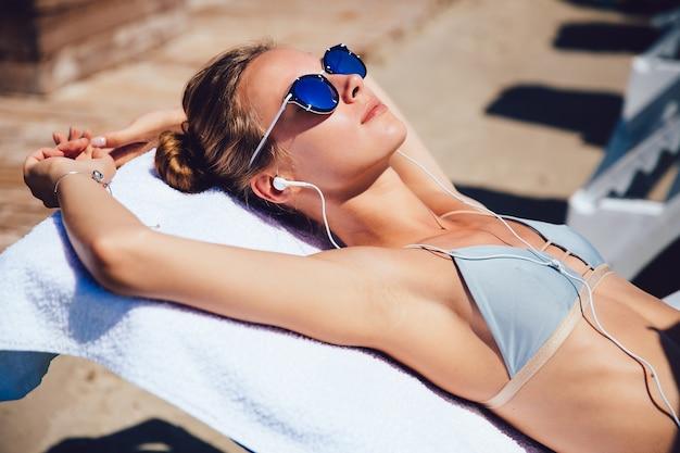 Mulher jovem e atraente em fato de banho e óculos de sol deitado numa espreguiçadeira, leva um bronzeado Foto gratuita