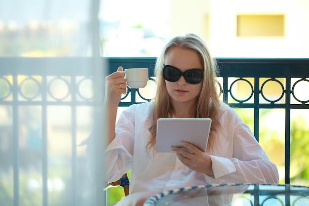 Mulher jovem e atraente em óculos de sol, lendo um tablet pc em uma varanda Foto Premium