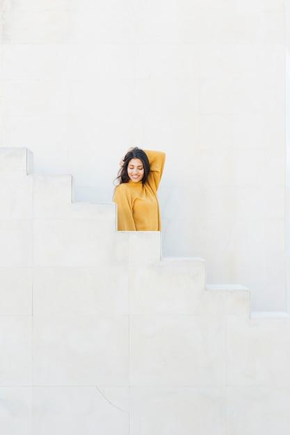Mulher jovem e atraente em pé na escada Foto gratuita