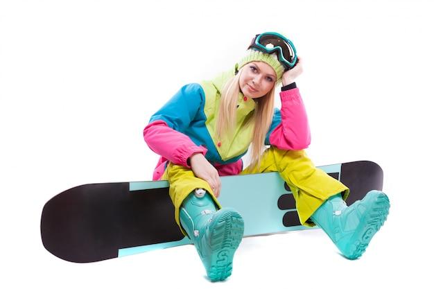 Mulher jovem e atraente em terno de esqui e óculos de esqui sentar no snowboard Foto Premium