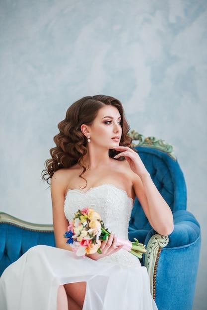 Mulher jovem e atraente em um vestido de noiva. noiva com o buquê interior Foto Premium