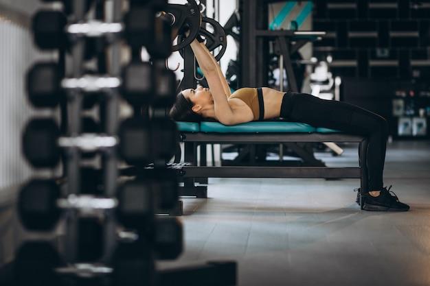 Mulher jovem e atraente exercitando na academia Foto gratuita