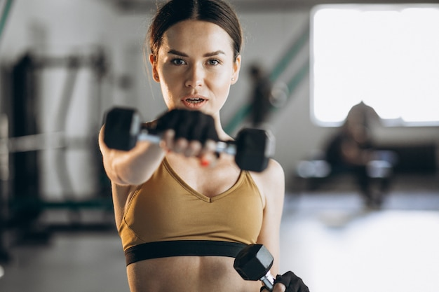 Mulher jovem e atraente exercitar com halteres na academia Foto gratuita