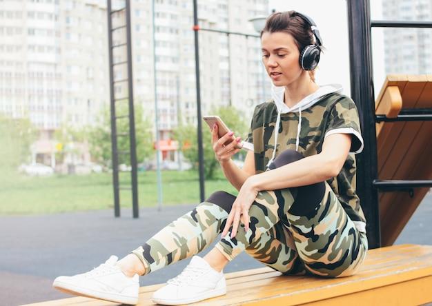 Mulher jovem e atraente forma em fones de ouvido e esporte colorido militar usam treinamento com celular Foto Premium