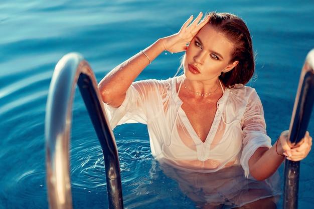 Mulher jovem e atraente na camisa branca molhada em uma piscina Foto Premium