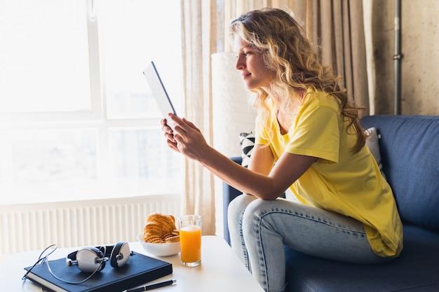 Mulher jovem e atraente sentada relaxada no sofá em casa segurando um tablet, assistindo online Foto gratuita