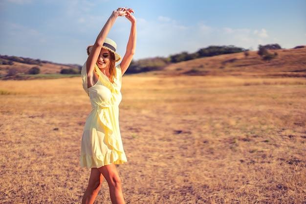 Mulher jovem e bonita ao ar livre na colina em um dia de verão Foto Premium