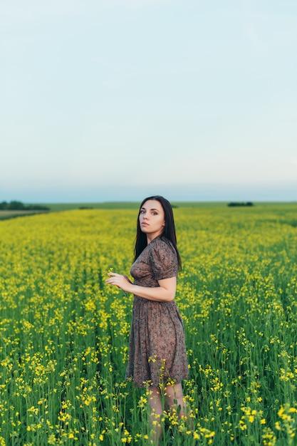 Mulher jovem e bonita ao pôr do sol no campo Foto Premium