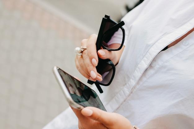 Mulher jovem e bonita bem sucedida elegante com óculos de sol e telefone celular nas mãos dela Foto Premium