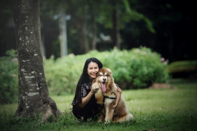 Mulher jovem e bonita brincando com seu cachorro pequeno em um parque ao ar livre. retrato do estilo de vida. Foto gratuita