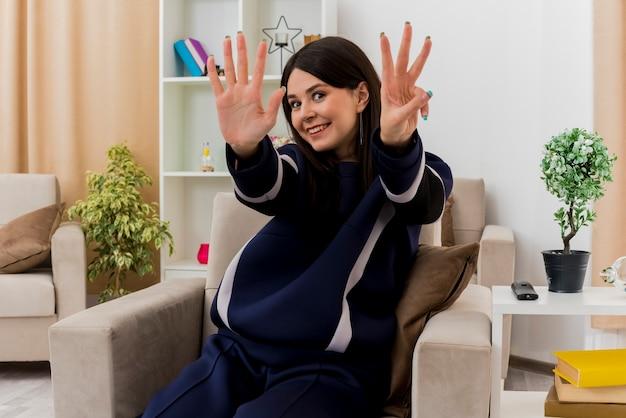 Mulher jovem e bonita caucasiana sorridente, sentada em uma poltrona em uma sala projetada, mostrando cinco e três com as mãos Foto gratuita