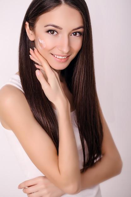 Mulher jovem e bonita com a pele limpa, fresca, toque seu rosto. tratamento facial. cosmetologia, beleza e spa. Foto Premium
