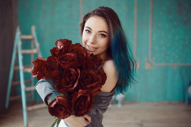Mulher jovem e bonita com buquê de rosas Foto gratuita