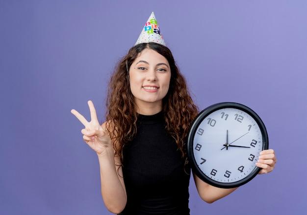 Mulher jovem e bonita com cabelo encaracolado com um boné de férias segurando um relógio de parede e sorrindo alegremente, mostrando o conceito de festa de aniversário com o sinal v em pé sobre a parede azul Foto gratuita