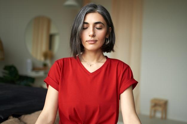 Mulher jovem e bonita com cabelo grisalho e argola no nariz meditando dentro de casa, usando a técnica de respiração Foto gratuita